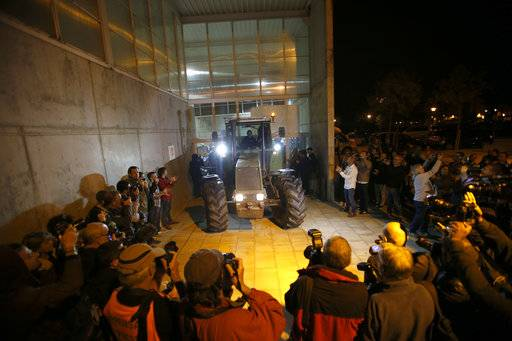 As journalists take pictures, a parked tractor blocks the door of a sports center, assigned to be a polling station by the Catalan government and where Catalan President Carles Puigdemont is expected to vote, in Sant Julia de Ramis, near Girona, Spain, Sunday, Oct. 1, 2017. Catalan pro-referendum supporters vowed to ignore a police ultimatum to leave the schools they are occupying to use in a vote seeking independence from Spain.