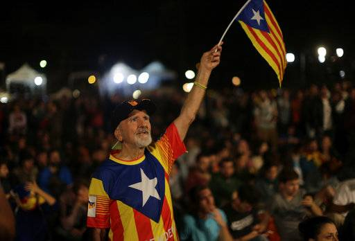 A man waves a ''estelada'' or Catalonia independence flag during a gathering at Plaza Catalonia in Barcelona, Spain, Sunday evening, 1 Oct. 2017. During the day Spanish riot police smashed their way into polling stations to try to halt a disputed independence referendum and fired rubber bullets at protesters.