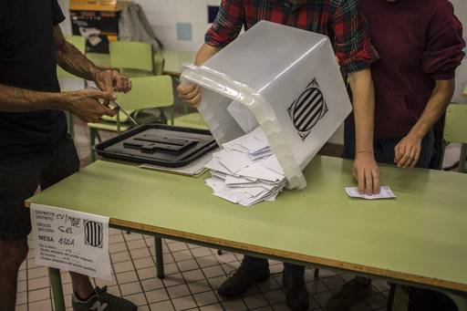 Officials empty a ballot box to count the votes at a school listed to be a polling station by the Catalan government in Barcelona, Spain, Sunday evening, Oct. 1, 2017. During the day Spanish riot police smashed their way into polling stations to try to halt a disputed independence referendum and fired rubber bullets at protesters.