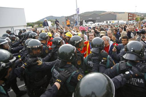 People block the street in a stand off with civil guards in Sant Julia de Ramis, near Girona, Spain, Sunday, Oct. 1, 2017. Scuffles have erupted as voters protested while dozens of anti-rioting police broke into a polling station where the regional leader was expected to show up for voting on Sunday.