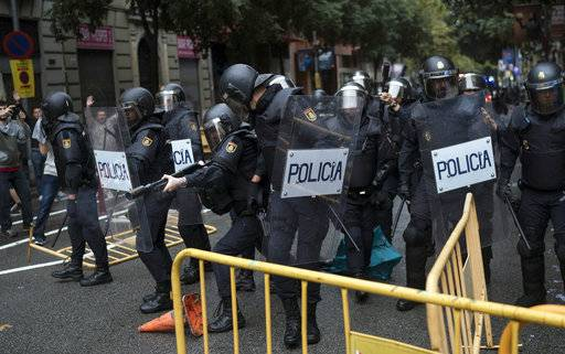 Spanish riot police removes fences thrown to them as one aims his rubber bullet rifle as they try to prevent people from reaching a voting site at a school assigned to be a polling station by the Catalan government in Barcelona, Spain, Sunday, 1 Oct. 2017. Catalan pro-referendum supporters vowed Saturday to ignore a police ultimatum to leave the schools they are occupying to use in a vote seeking independence from Spain.