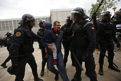 Civil guards force a man with a child to leave the entrance of a sports center, assigned to be a referendum polling station by the Catalan government in Sant Julia de Ramis, near Girona, Spain, Sunday, Oct. 1, 2017. Scuffles have erupted as voters protested as dozens of anti-rioting police broke into a polling station where the regional leader was expected to show up for voting on Sunday.
