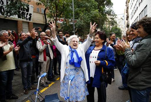 An elderly lady is applauded as she celebrates after voting at a school assigned to be a polling station by the Catalan government at the Gracia neighborhood in Barcelona, Spain, Sunday, 1 Oct. 2017. The Spanish government and its security forces are trying to prevent voting in the independence referendum, which is backed by Catalan regional authorities. Spanish officials had said force wouldn't be used, but that voting wouldn't be allowed.