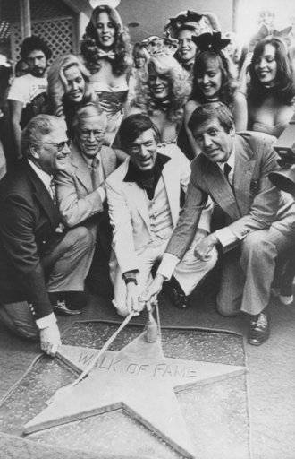 "FILE - In this April 10, 1980, file photo, Chairman of the Board, Playboy Enterprises Inc., Hugh Hefner, center, receives a star on the Hollywood Walk of Fame in Los Angeles. Honorary Mayor of Hollywood, Monty Hall, right, holds the rope attached to the new star with Hefner. Former ""Let's Make a Deal"" host Hall has died after a long illness at age 96. His daughter Sharon Hall says he died Saturday, Sept. 30, 2017, at his home in Beverly Hills, Calif."