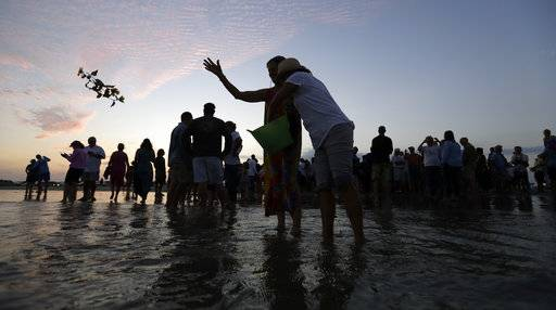 Flowers are tossed in to ocean after a sea turtle with along with the ashes of renowned oceanographer Tony Amos were released into the Gulf of Mexico following a memorial service, Saturday, Sept. 30, 2017, in Port Aransas, Texas. Amos, 80, died of complications from prostate cancer on Sept. 4, mere days after Harvey roared ashore as a fearsome hurricane.