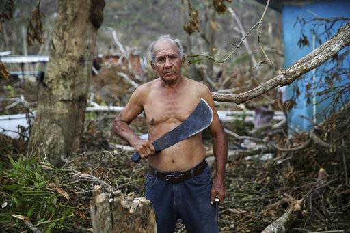 In this Sept. 29, 2017 photo, U.S. Army veteran Luis Cabrera Sanchez holds his machete as he pauses for a portrait while clearing debris from his damaged home, with family and neighbors, in the aftermath of Hurricane Maria in Yabucoa, Puerto Rico. Sanchez, who served in the military from 1966 to 1969, said his greatest needs are water, food and energy.