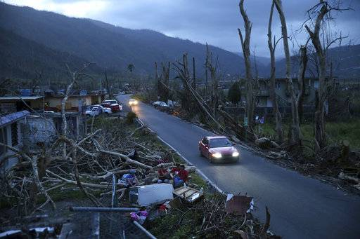 In this Sept. 26, 2017 photo, neighbors sit on a couch outside their destroyed homes as sun sets in the aftermath of Hurricane Maria, in Yabucoa, Puerto Rico. For decades AP journalists have worked in challenging conditions covering news around the world, but rarely have they had to navigate such constant shortages, blackouts and communications outages on U.S. soil.