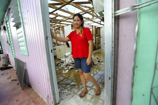 "In this Sept. 29, 2017 photo, Sandy Nieves poses for a portrait in the door of her heavily damaged home in the aftermath of Hurricane Maria in Yabucoa, Puerto Rico. Nieves said her greatest need is her home and especially her baby's bed. ""We don't have anywhere to sleep, we don't have our stuff. We are all sleeping in one bed at my mom's house."""