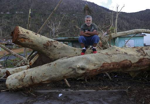 "In this  Sept. 29, 2017 photo, Martin Ruiz poses for a portrait on a fallen tree in his neighborhood in the aftermath of Hurricane Maria in Yabucoa, Puerto Rico. ""After the hurricane, what I want is help for the people who are in the most devastated areas. In my case, there were no problems. In my home there was very little damage. But there are other relatives, who lost their home, their clothes, and they are need.  For the moment I am fine."""