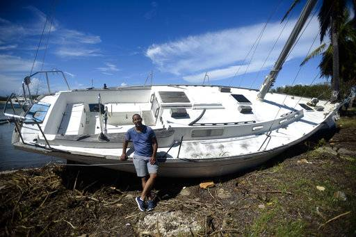"This Sept. 29, 2017 photo shows Rafael Velazquez, a resident of Cayey, posing for a portrait next to his boat lying on the bank after the storm surge brought by Hurricane Maria in Santa Isabel, Puerto Rico. Velazquez, who is applying to study his doctorate in chemical physics at the University of Puerto Rico, said his greatest need is to put the boat back in the water. ""I bought it a year ago and hadn't used it yet. The storm premiered it for me,"" said Velazquez."