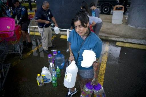 "Emari Rodriguez poses for a portrait after filling up bottles at a water distribution center to take it home, which is intact, but lacks water and electricity, in the wake of Hurricane Maria in Bayamon, Puerto Rico, Thursday, Sept. 28, 2017. Rodriguez, who lacks water and electricity at home, but which is still in tact, said she's most worried about the elderly in her neighborhood. ""We need the electricity to return, since the elderly won't hold up much more with this situation. We need to move forward."""