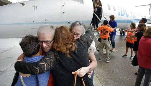 Angel and Ana Delgado hug family members after arriving at Fort Lauderdale/Hollywood International Airport, Friday, Sept. 29, 2017, on an IBC Airways flight that evacuated seniors from Puerto Rico. The flight was provided by a local nonprofit organization, the Pathfinders Task Force, through a program called Eagles Wings. (Michael Laughlin/South Florida Sun-Sentinel via AP)