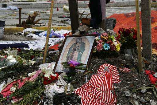 In this Wednesday, Sept. 27, 2017 photo, a framed image of Mexico's patron saint, the Virgin of Guadalupe, makes up part of a memorial for those who died when a five-story office and factory building was collapsed by a recent earthquake on 168 Bolivar Street, in the Obrera neighborhood of Mexico City. The rubble from the Sept. 19th earthquake has been cleared, only the concrete foundation with the building's footprint and memorial remain.