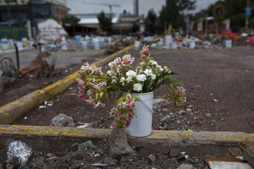 A five-gallon bucket which volunteer rescuers had used to carefully remove rubble in the first days of the rescue attempts serves as a vase for a fresh spray of flowers at 168 Bolivar Street, a collapsed five-story office and factory building in the the Obrera neighborhood of Mexico City, Friday, Sept. 29, 2017. On sidewalks, median strips and amid the brick dust, mud and rubble of the 38 buildings that collapsed in Mexico's 7.1 earthquake, impromptu memorials to victims and rescuers have sprung up, as the capital begins to come to terms with its losses.