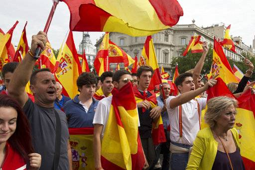 People wave Spanish national flags as thousands packed the central Cibeles square to in Madrid, Spain, Saturday, Sept. 30, 2017. Thousands of pro-Spanish unity supporters donning Spanish flags have rallied in a central Madrid plaza to protest the Catalan regional government's drive to separate from Spain.