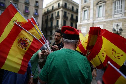 A man hands out Spanish flags to people demonstrating against Catalonia's planned referendum on secession in Barcelona Saturday, Sept. 30 2017. The planned referendum is due to be held Sunday by the pro-independence Catalan government but Spain's government calls the vote illegal, since it violates the constitution, and the country's Constitutional Court has ordered it suspended.