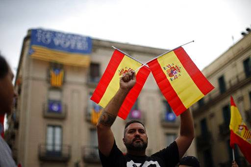 A man holds Spanish flags while demonstrating against Catalonia's planned referendum on secession, in front of a building decorated with pro-independence banners, in Barcelona Saturday, Sept. 30 2017. The planned referendum is due to be held Sunday by the pro-independence Catalan government but Spain's government calls the vote illegal, since it violates the constitution, and the country's Constitutional Court has ordered it suspended.
