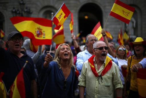 People wave Spanish flags while demonstrating against Catalonia's planned referendum on secession in Barcelona Saturday, Sept. 30 2017. The planned referendum is due to be held Sunday by the pro-independence Catalan government but Spain's government calls the vote illegal, since it violates the constitution, and the country's Constitutional Court has ordered it suspended.