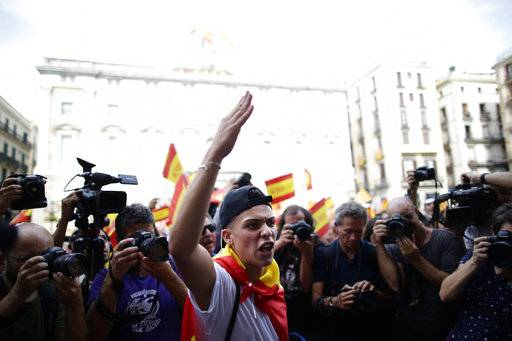 A young man wrapped in a Spanish flag gestures while demonstrating against Catalonia's planned referendum on secession in Barcelona Saturday, Sept. 30 2017. The planned referendum is due to be held Sunday by the pro-independence Catalan government but Spain's government calls the vote illegal, since it violates the constitution, and the country's Constitutional Court has ordered it suspended.