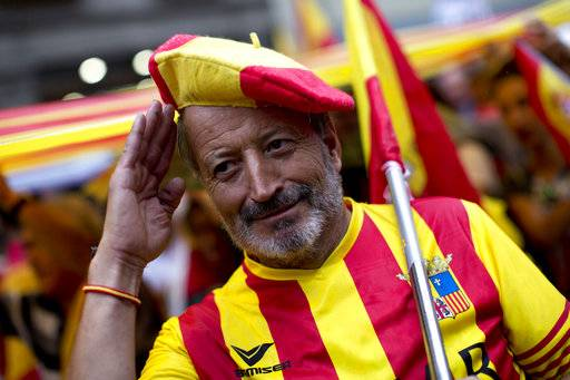 An anti-independence demonstrator salutes for the camera as they march waving Spanish flags against the referendum downtown Barcelona Saturday, Sept. 30 2017. The planned referendum is due to be held Sunday by the pro-independence Catalan government but Spain's government calls the vote illegal, since it violates the constitution, and the country's Constitutional Court has ordered it suspended.