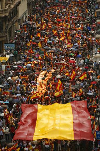 Protesters wrapped in red and yellow regional and national colors display a giant Spanish flag over their heads while marching to defend the unity of Spain and against a disputed referendum on the region's independence that separatist politicians want to hold Sunday, in Barcelona Saturday, Sept. 30 2017. Catalonia's planned referendum on secession is due to be held Sunday by the pro-independence Catalan government but Spain's government calls the vote illegal, since it violates the constitution, and the country's Constitutional Court has ordered it suspended.