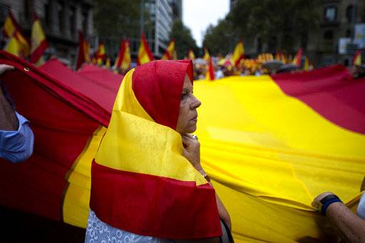 Anti-independence demonstrators march waving Spanish flags against the referendum downtown Barcelona Saturday, Sept. 30 2017. The planned referendum is due to be held Sunday by the pro-independence Catalan government but Spain's government calls the vote illegal, since it violates the constitution, and the country's Constitutional Court has ordered it suspended.