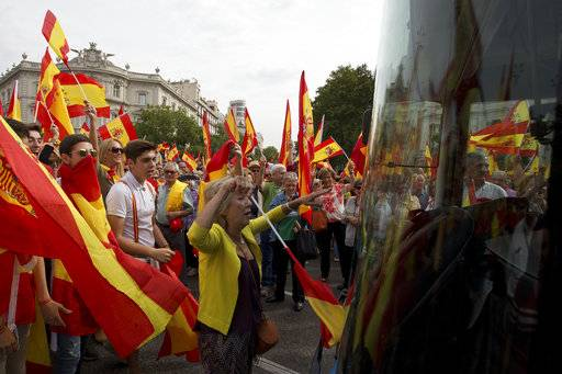 People waving Spanish national flags block the path of a bus as thousands packed the central Cibeles square in Madrid, Spain, Saturday, Sept. 30, 2017. Thousands of pro-Spanish unity supporters donning Spanish flags have rallied in a central Madrid plaza to protest the Catalan regional government's drive to separate from Spain.
