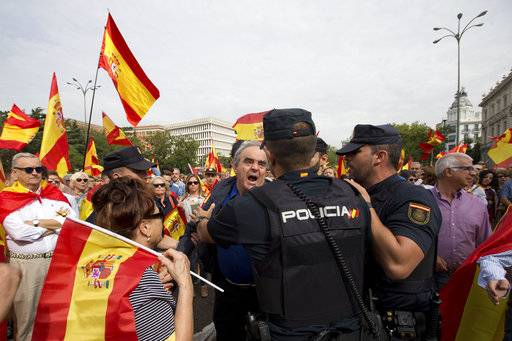 A man shouts at police officers as thousands packed the central Cibeles square in Madrid, Spain, Saturday, Sept. 30, 2017. Thousands of pro-Spanish unity supporters donning Spanish flags have rallied in a central Madrid plaza to protest the Catalan regional government's drive to separate from Spain.