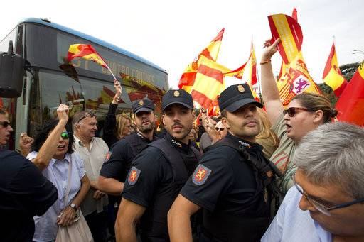 Police officers intervene as crowds block traffic in central Cibeles square in Madrid, Spain, Saturday, Sept. 30, 2017. Thousands of pro-Spanish unity supporters donning Spanish flags have rallied in a central Madrid plaza to protest the Catalan regional government's drive to separate from Spain.