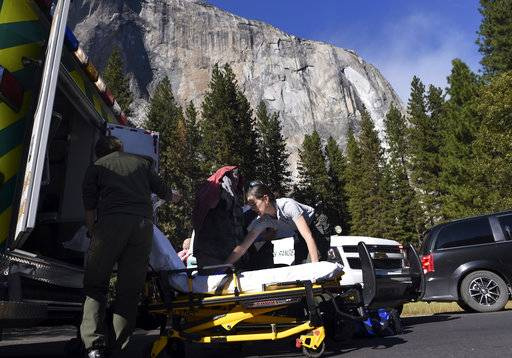 Emergency personnel prepare to care for an elderly male, center background, after a rock fall occurred again on El Capitan Thursday afternoon, Sept. 28, 2017 in Yosemite National Park, Calif. Yosemite National Park says another rock fall has injured one person in the park, one day after a huge chunk of granite killed a British tourist. An immense mass of granite plunged from the side of El Capitan on Thursday and filled the valley below with a cloud of dust. (Eric Paul Zamora/The Fresno Bee via AP)