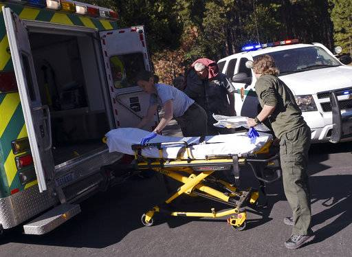 Emergency personnel prepare to care for an elderly man, center background, who was injured after a new rock fall on El Capitan occurred Thursday afternoon, Sept. 28, 2017, in Yosemite National Park, Calif. The fall came a day after tons of rock crashed down from El Capitan, killing a tourist who had been on a hiking and climbing trip and injuring a British woman with him. (Eric Paul Zamora/The Fresno Bee via AP)