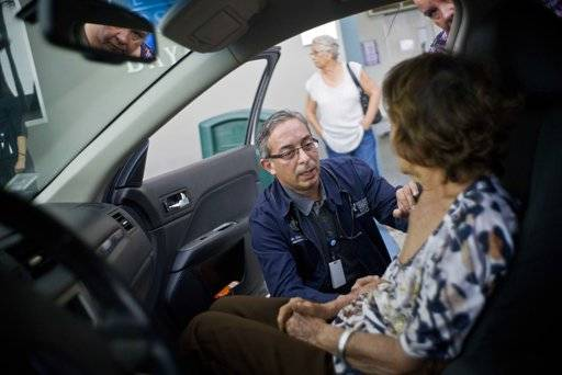 In this Thursday, Sept. 28, 2017 photo, Dr. Victor Rivera attends Carmen Hernandez in a car in the hospital's parking lot for lack of space at the hospital in Bayamon, Puerto Rico. Hurricane Maria is stressing Puerto Rico's already weak health care system. Rivera said they are so overwhelmed that he has been intercepting patients in the ER waiting room and even outside while people are still in their cars, to send them on their way with medical advice or a prescription in non-emergency cases.