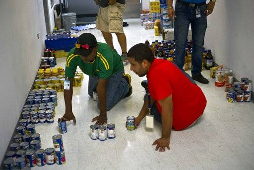 Hospital employees sort donated canned food to deliver to a nearby shelter for hurricane victims, in Catano, Puerto Rico, Thursday, Sept. 28, 2017. The aftermath of the powerful storm has resulted in a near-total shutdown of the U.S. territory's economy that could last for weeks and has many people running seriously low on cash and worrying that it will become even harder to survive on this storm-ravaged island.
