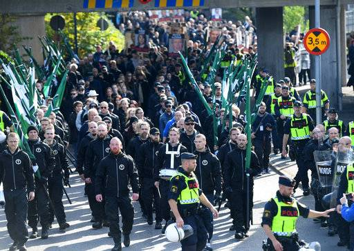Members of the Nordic Resistance Movement march in central Goteborg, Sweden, Saturday Sept. 30, 2017. The authorities say the Nordic Resistance Movement expects some 1,000 people to march Saturday while as many as 10,000 people could counter-demonstrate. (Fredrik Sandberg/TT via AP)