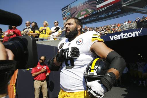 FILE - In this Sept. 24, 2017, file photo, Pittsburgh Steelers offensive tackle and former Army Ranger Alejandro Villanueva (78) stands outside the tunnel alone during the national anthem before an NFL football game against the Chicago Bears in Chicago. The AP reported on Sept. 29, 2017, that a report claiming Steelers players were fined $1 million for skipping the national anthem was false.