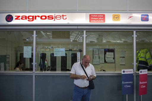 A traveler checks his phone in front of a Kurdish airline ticket office at the Irbil International Airport in Iraq Friday, Sept. 29, 2017. Many travelers boarded the last flights out of the cities of Irbil and Sulaymaniyah as an Iraqi government order to halt all international flights in Kurdish territory was set to kick in on Friday.