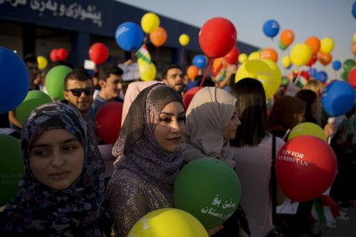 Kurdish women hold balloons to protest against the flight ban issued by the Iraq federal government outside the Irbil International Airport in Iraq, Friday, Sept. 29, 2017. Many travelers boarded the last flights out of the cities of Irbil and Sulaymaniyah as an Iraqi government order to halt all international flights in Kurdish territory was set to kick in on Friday.