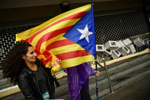"A pro independence supporter holds an ""estelada"", or Catalan pro independence flag, next to mock ballots boxes, right, during a rally in support of the Catalonia's secession referendum, in Bilbao, northern Spain, Saturday, Sept. 30, 2017. Catalonia's planned referendum on secession is due to be held Sunday by the pro-independence Catalan government but Spain's government calls the vote illegal, since it violates the constitution, and the country's Constitutional Court has ordered it suspended."