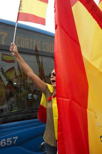 A woman waving a Spanish national flag blocks the path of a bus as thousands packed the central Cibeles square in Madrid, Spain, Saturday, Sept. 30, 2017. Thousands of pro-Spanish unity supporters donning Spanish flags have rallied in a central Madrid plaza to protest the Catalan regional government's drive to separate from Spain.