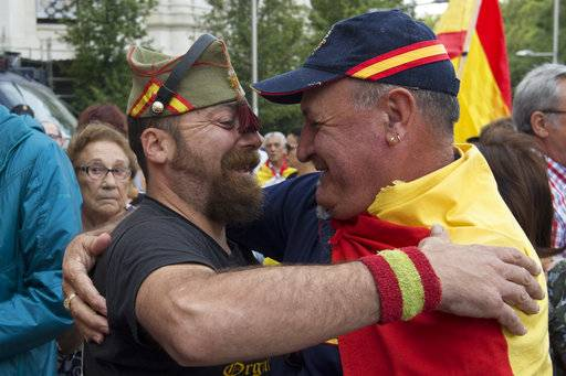 A man in a legionnaires uniform hugs a man draped in a Spanish flag as thousands packed the central Cibeles square to in Madrid, Spain, Saturday, Sept. 30, 2017. Thousands of pro-Spanish unity supporters donning Spanish flags have rallied in a central Madrid plaza to protest the Catalan regional government's drive to separate from Spain.