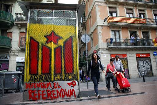 People walk past a graffiti of a Gracia neighborhood pro-independence youth organization in Barcelona Saturday, Sept. 30 2017. Catalonia's planned referendum on secession is due to be held Sunday by the pro-independence Catalan government but Spain's government calls the vote illegal, since it violates the constitution, and the country's Constitutional Court has ordered it suspended.