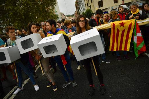 "Pro independence supporters carry mock ballot boxes, with an ""estelada"", or Catalan pro independence flag, and an ""Ikurrina"", or Basque regional flag, right, during a rally in support of the Catalonia's secession referendum, in Bilbao, northern Spain, Saturday, Sept. 30, 2017. Catalonia's planned referendum on secession is due to be held Sunday by the pro-independence Catalan government but Spain's government calls the vote illegal, since it violates the constitution, and the country's Constitutional Court has ordered it suspended."