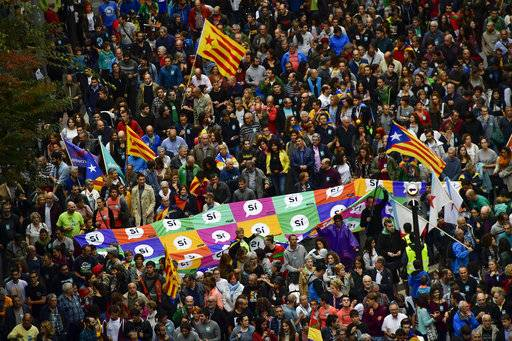"Pro independence supporters carry a giant banner reading ''Yes'' as they wave ""esteladas"", or Catalan pro independence flags, during  a rally in support of the Catalonia's secession referendum, in Bilbao, northern Spain, Saturday, Sept. 30, 2017. Catalonia's planned referendum on secession is due to be held Sunday by the pro-independence Catalan government but Spain's government calls the vote illegal, since it violates the constitution, and the country's Constitutional Court has ordered it suspended."