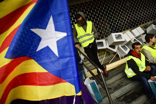 "Pro independence supporters stand beside mock ballot boxes close to an ""estelada"", or Catalan pro independence flag, during a rally in support of the Catalonia's secession referendum, in Bilbao, northern Spain, Saturday, Sept. 30, 2017. Catalonia's planned referendum on secession is due to be held Sunday by the pro-independence Catalan government but Spain's government calls the vote illegal, since it violates the constitution, and the country's Constitutional Court has ordered it suspended."