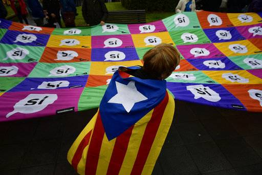 A pro independence supporter with an ''estelada'', or Catalan pro independence flag, on her back grabs a giant banner reading, ''Yes'' during a rally in support of the Catalonia's secession referendum, in Bilbao, northern Spain, Saturday, Sept. 30, 2017. Catalonia's planned referendum on secession is due to be held Sunday by the pro-independence Catalan government but Spain's government calls the vote illegal, since it violates the constitution, and the country's Constitutional Court has ordered it suspended.