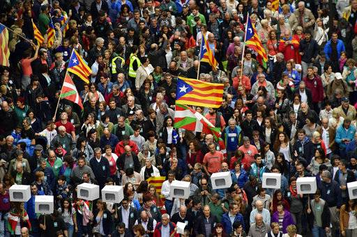 "Pro independence supporters carrying mock ballot boxes and ""esteladas"", or Catalan pro independence flags, top, with ""ikurrinas"", or Basque flags, take part in a rally in support for the Catalonia's secession referendum, in Bilbao, northern Spain, Saturday, Sept. 30, 2017. Catalonia's planned referendum on secession is due to be held Sunday by the pro-independence Catalan government but Spain's government calls the vote illegal, since it violates the constitution, and the country's Constitutional Court has ordered it suspended."