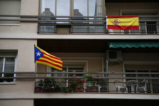 A Spanish flag, right, and an ''estelada'' or Catalonia independence flag hang on balconies of a building in Barcelona Saturday, Sept. 30 2017. Catalonia's planned referendum on secession is due to be held Sunday by the pro-independence Catalan government but Spain's government calls the vote illegal, since it violates the constitution, and the country's Constitutional Court has ordered it suspended.