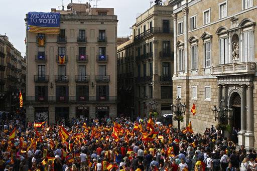 People wave Spanish flags while demonstrating against Catalonia's planned referendum on secession, in front of a building decorated with pro-independence banners, in Barcelona Saturday, Sept. 30 2017. The planned referendum is due to be held Sunday by the pro-independence Catalan government but Spain's government calls the vote illegal, since it violates the constitution, and the country's Constitutional Court has ordered it suspended.