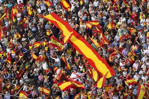 "People wave Spanish national flags as thousands packed the central Cibeles square to in Madrid, Spain, Saturday, Sept. 30, 2017. Thousands of pro-Spanish unity supporters donning Spanish flags have rallied in a central Madrid plaza to protest the Catalan regional government's drive to separate from Spain. Writing on one of the flags reads: ""Long live the Unity of Spain""."