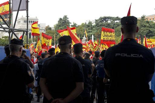 Police block the entrance of the city hall as protesters wave Spanish national flags in the central Cibeles square in Madrid, Spain, Saturday, Sept. 30, 2017. Thousands of pro-Spanish unity supporters donning Spanish flags have rallied in a central Madrid plaza to protest the Catalan regional government's drive to separate from Spain.